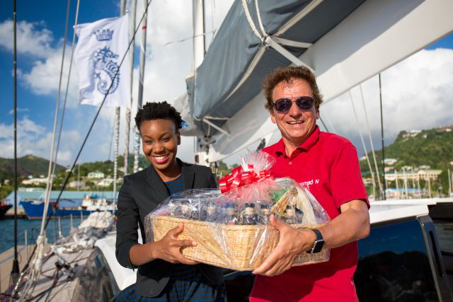 Chrislyn Lashington, Grenada Tourism Authority, presents Jean-Paul Riviere with a basket of Grenadian specialities, including Westerhall Rums, Grenadian Chocolate and Spice. Photo:RORC/Arthur Daniel