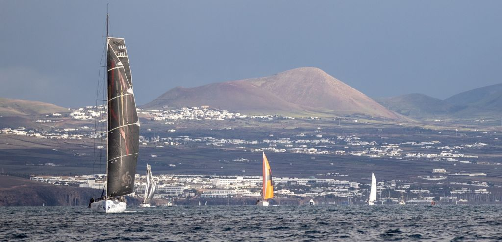 The dramatic volcanic mountains of Lanzarote make an impressive backdrop as the RORC Transatlantic Race fleet head for the Caribbean © James Mitchell